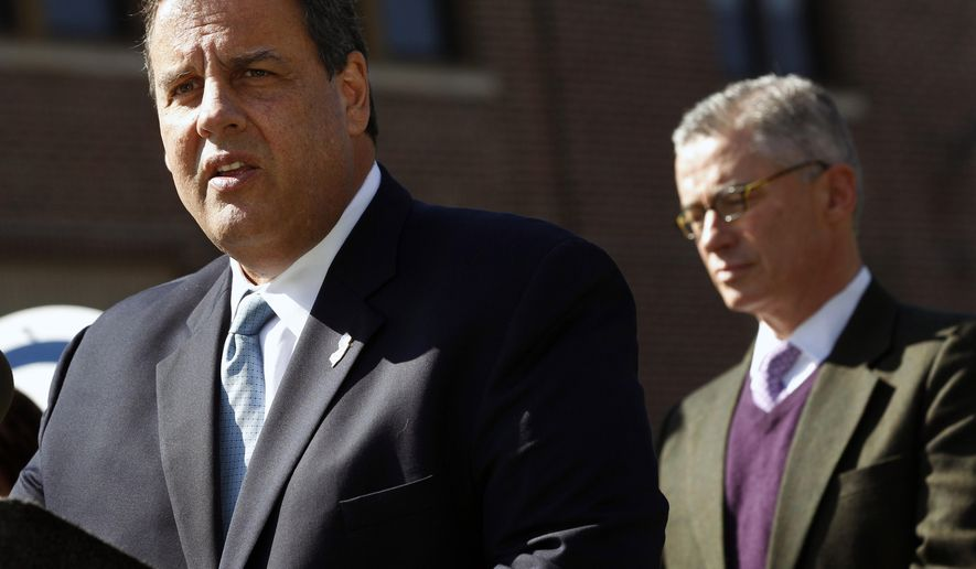 Former Gov. Jim McGreevey, right, listens as Gov. Chris Christie addresses a gathering about plans for better treatment for those in the state with addiction and mental health problems Thursday, Oct. 9, 2014, in Trenton, N.J. When he's not campaigning for politicians elsewhere, Christie has often been campaigning in New Jersey for more services for people with addictions. (AP Photo/Mel Evans)