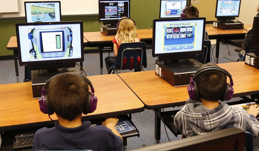 FILE  In this July 21, 2014 file photo, students at a summer reading academy at Buchanan elementary school work in the computer lab at the school in Oklahoma City. The Oklahoma Supreme Court has confirmed the Legislature was well within its authority to repeal a set of education standards in math and English known as Common Core. But what's still uncertain is whether reverting back to the old academic standards will put Oklahoma students at a disadvantage when competing against those in more than 40 other states who are moving ahead with the more advanced and rigorous new ones developed under Common Core. A much-needed overhaul of American public education _ new methods of teaching English and math and redesigned testing _ was sponsored by U.S. state governors five years ago and has been adopted in nearly every state. Now the program to make U.S. students more competitive with global counterparts is caught in bitter partisan divisions in the country where some politicians are trying to win support from voters who are mad at Washington. (AP Photo/Sue Ogrocki, File)