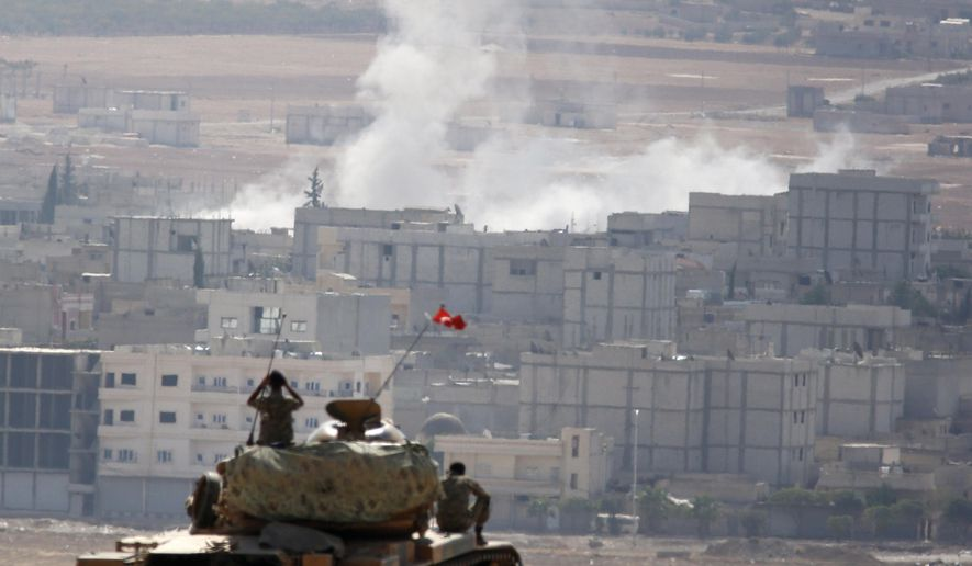 Turkish soldiers on a tank and an armoured vehicle hold their positions on a hilltop in the outskirts of Suruc, Turkey, at the Turkey-Syria border, overlooking smoke rising from a strike in Kobani, Syria, during fighting between Syrian Kurds and the militants of Islamic State group, Thursday, Oct. 9, 2014. Kobani, also known as Ayn Arab, and its surrounding areas, has been under assault by extremists of the Islamic State group since mid-September and is being defended by Kurdish  fighters.(AP Photo/Lefteris Pitarakis)