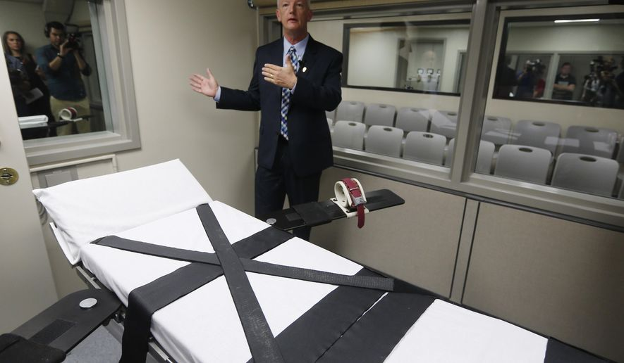 The gurney in the newly renovated death chamber at the Oklahoma State Penitentiary is pictured during a media tour of the facility in McAlester, Okla, Thursday, Oct. 9, 2014. At rear is Department of Corrections official Scott Crow, and behind him is the witness room. (AP Photo/Sue Ogrocki)
