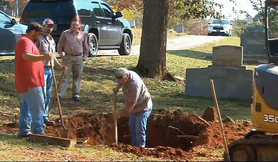 """In this photo made from video and released by WSFA-TV, workers labor to exhume the body of a John Doe buried in Alabama in 1981, in Scottsboro, Ala. on Thursday, Oct. 9, 2014. The FBI is exhuming the body of a John Doe buried in Alabama in 1981 in its search for a 10 Most Wanted Fugitive accused of killing his family with a sledgehammer nearly 40 years ago. In court filings, the FBI said there is a strong resemblance between photos of the John Doe and former State Department diplomat William Bradford """"Brad"""" Bishop Jr.  (AP Photo/WAFF-TV)"""