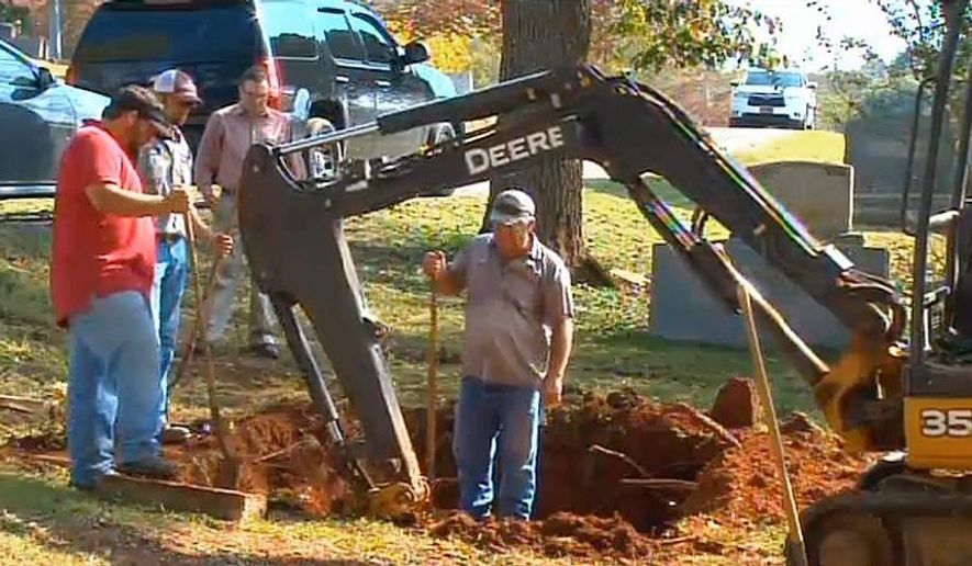 "In this photo made from video and released by WAFF-TV, workers labor to exhume the body of a John Doe buried in Alabama in 1981, in Scottsboro, Ala. on Thursday, Oct. 9, 2014. The FBI is exhuming the body of a John Doe buried in Alabama in 1981 in its search for a 10 Most Wanted Fugitive accused of killing his family with a sledgehammer nearly 40 years ago. In court filings, the FBI said there is a strong resemblance between photos of the John Doe and former State Department diplomat William Bradford ""Brad"" Bishop Jr.  (AP Photo/WAFF-TV)"