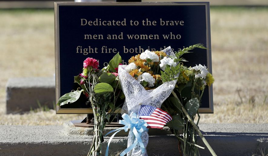"Flowers are seen at a plaque honoring ground and air firefighters at the California Department of Forestry and Fire Protection Aviation Management facility at McClellan Air Park, in Sacramento, Calif., Wednesday Oct. 8, 2014.  Air tanker pilot Geoffrey, ""Craig"" Hunt,  was killed Tuesday while fighting the Dog Rock Fire in Yosemite National Park.   Hunt, 62, a 13-year veteran pilot of Dyncorp International, was flying an S-2T air tanker under contract with the state, when his plane hit a canyon wall.  CalFire has temporarily grounded itss fleet of S-2T's for inspection. (AP Photo/Rich Pedroncelli)"