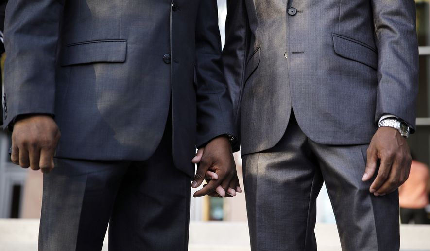 Sherwood Howard, right, and Nevada State Sen. Kelvin Atkinson hold hands before they get married outside of the Marriage License Bureau, Thursday, Oct. 9, 2014, in Las Vegas. The two had just obtained a same-sex marriage license and were the first same-sex couple married in Las Vegas. (AP Photo/John Locher)