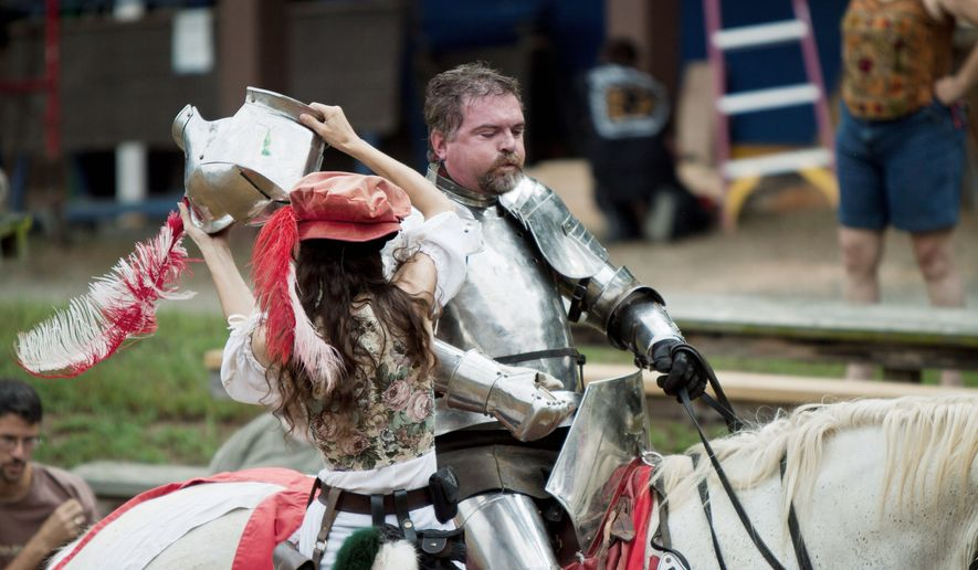 "One of the Renaissance Festival's fair maidens helps Leland Coleman get his armor on before heading into ""combat"" with the Free Lancers. (Pratik Shah/The Washington Times)"
