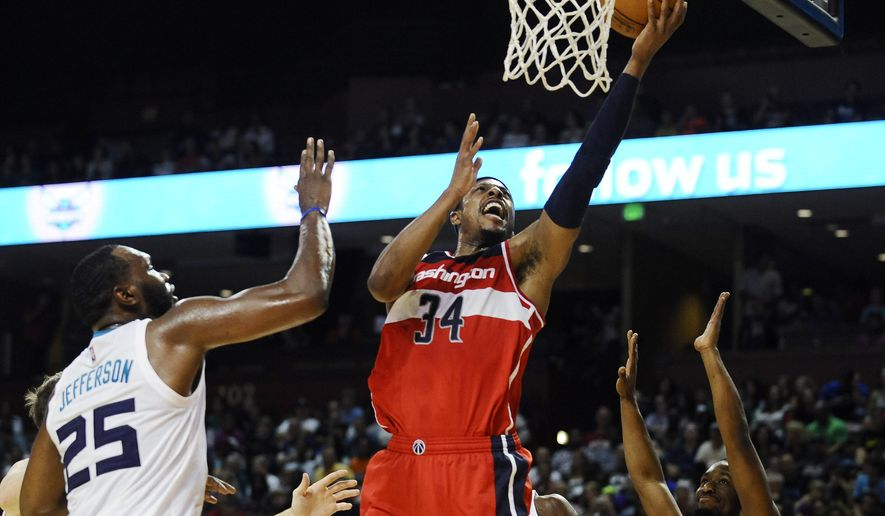 Washington Wizards forward Paul Pierce (34) looks to score as Charlotte Hornets center Al Jefferson (25) and Charlotte Hornets guard Kemba Walker (15) defend during the first half of a preseason NBA basketball game, Friday, Oct. 10, 2014, in Greenville, S.C. (AP Photo/Rainier Ehrhardt)