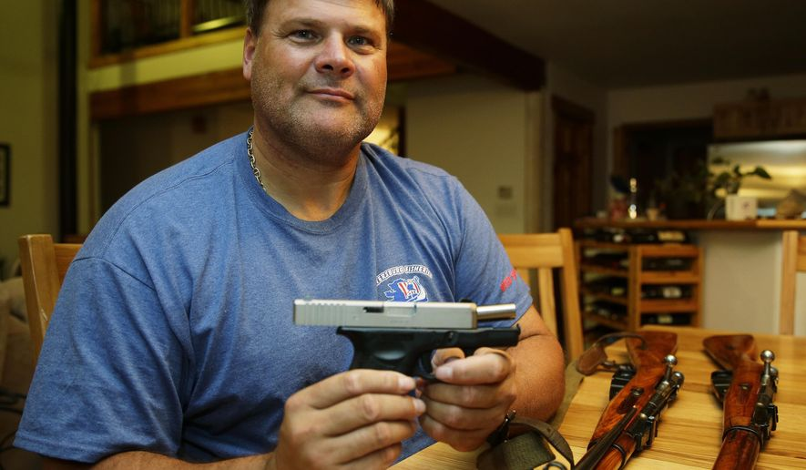 In this photo taken Oct. 7, 2014, Kurt Heikkila poses for a photo with his handgun, which he has a permit to carry while concealed, as well as several Russian-made rifles that he collects, in his home in Tenino, Wash. Heikkila says he will vote against Initiative 594, which is seeking universal background checks on gun sales and transfers, with some exceptions because he believes the measure goes too far. (AP Photo/Ted S. Warren)