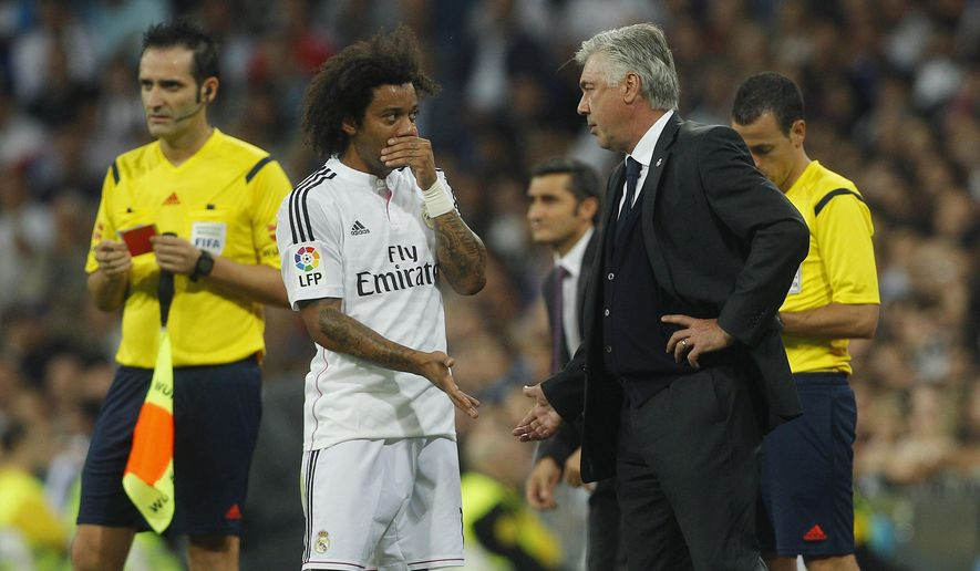 Real's coach Carlo Ancelotti, center right, talks to Marcelo, center left, during a Spanish La Liga soccer match between Real Madrid and Athletic Bilbao at the Santiago Bernabeu stadium in Madrid, Spain, Sunday, Oct. 5, 2014. (AP Photo/Andres Kudacki)