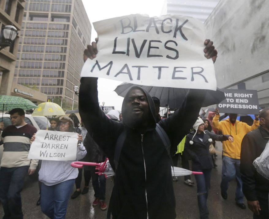 Protesters carry signs as they march in the streets of Clayton, Mo. on Friday, Oct. 10, 2014 near the St. Louis County Courthouse during a protest against the Aug. 9, 2014 police shooting of unarmed black 18-year-old Michael Brown in Ferguson, Mo. Protesters want prosecutors to file criminal charges against the white police officer who fatally shot Brown. (AP Photo/Charles Rex Arbogast)