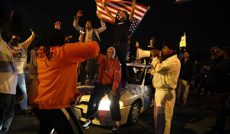 Protesters block a street Thursday, Oct. 9, 2014, a day after Vonderrit D. Myers was shot and killed by white, off-duty St. Louis police officer in St. Louis. Police say Myers was shot Wednesday after he opened fire on the off-duty officer, but Myers' parents say he was unarmed. (AP Photo/Jeff Roberson)