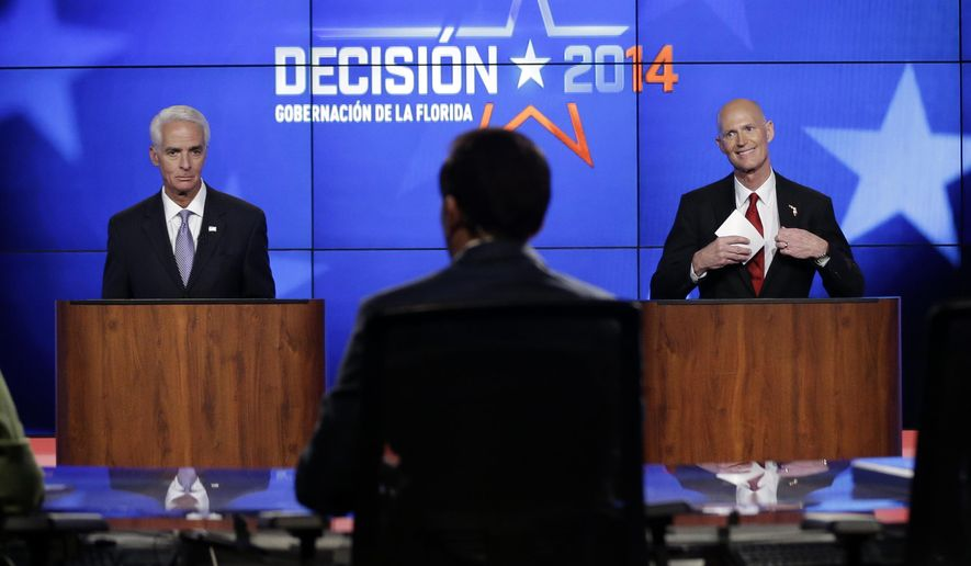 Democrat Charlie Crist, a former Republican governor of Florida, left, and Florida Republican Gov. Rick Scott, right, prepare to leave after a gubernatorial debate at the Spanish-language network Telemundo 51, Friday, Oct. 10, 2014, in Miramar, Fla. This is the first of three debates before the November election. (AP Photo/Lynne Sladky)