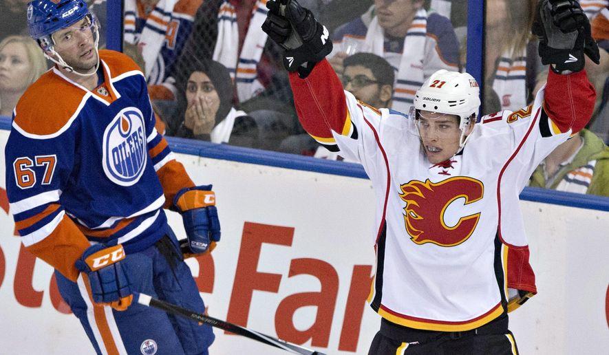Calgary Flames' Mason Raymond (21) celebrates a goal as Edmonton Oilers' Benoit Pouliot (67) looks on during third period NHL hockey action in Edmonton, Alberta, on Thursday Oct.9, 2014. (AP Photo/The Canadian Press, Jason Franson)