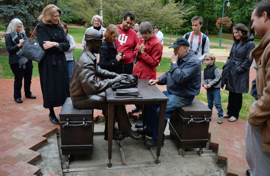 In this photo taken on Thursday, Oct. 9, 2014, artist Tuck Langland demonstrates how he envisioned visitors could sit at the desk with Ernie Pyle during the installation of the bronze Ernie Pyle statute outside Franklin Hall at Indiana University in Bloomington, Ind. The statue depicts Pyle sitting on an ammunition box with his typewriter, notes and a coffee cup on a table. (AP Photo/The Herald-Times,  Chris Howell)