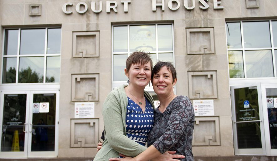 In this photo provided by Liz Dickinson, Kelli, left, and Angela pose for a picture after their wedding ceremony at the Johnson County Court House in Olathe, Kan., Friday, Oct. 10, 2014. The Johnson County newlyweds asked to be identified only by their first names to help protect their privacy, but did agree to allow a photograph of them after the ceremony to be used. In a statement released through the gay-rights group Equality Kansas, they said they wanted to celebrate privately. (AP Photo/piperlucyphotography.org, Liz Dickinson)