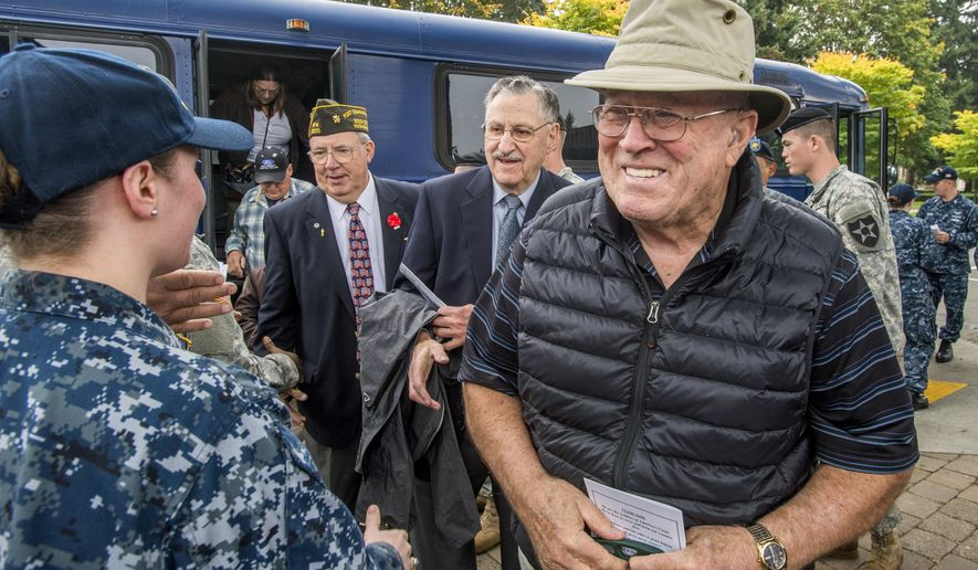 Marvin Merritt of Lacey and other Vietnam Veterans are welcomed off a bus by active-duty army and navy personnel before a day-long salute to Vietnam-era veterans at Joint Base Lewis McChord, Thursday, Oct. 9, 2014.  It part of the 50th Anniversary Commemoration of the Vietnam War. (AP photo/ The News Tribune, Peter Haley)