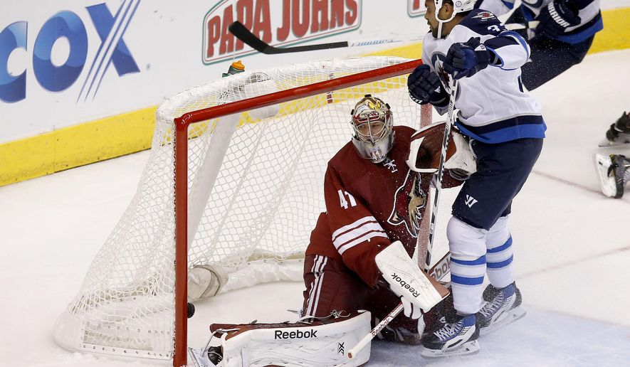 Winnipeg Jets' Dustin Byfuglien, right, scores against Arizona Coyotes' Mike Smith (41) during the second period of an NHL hockey game Thursday, Oct. 9, 2014, in Glendale, Ariz. (AP Photo/Ross D. Franklin)