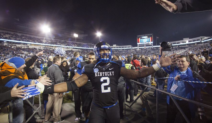 Kentucky defensive end Alvin Dupree celebrates as he leaves the field after Kentucky defeated South Carolina 45-38 during an NCAA college football game in Lexington, Ky., Saturday, Oct. 4, 2014. (AP Photo/David Stephenson)