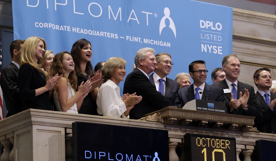 Diplomat Pharmacy's Chairman and CEO Phil Hagerman, fourth from right, is applauded as he rings the New York Stock Exchange opening bell, to mark his company's IPO, Friday, Oct. 10, 2014. Major U.S. stock indexes got off to an uneven start in early trading Friday, a day after stocks clocked their worst day of the year. (AP Photo/Richard Drew)