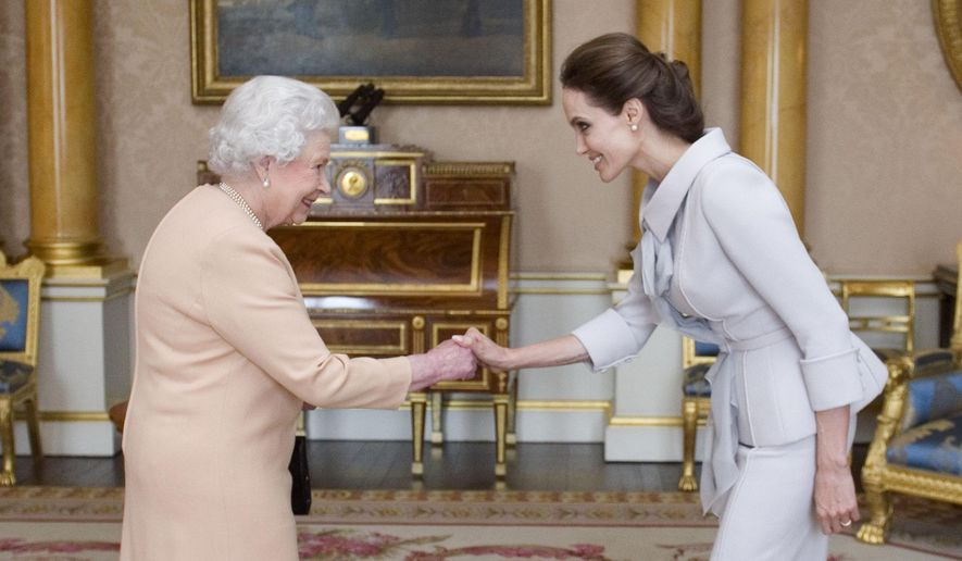 U.S. actress Angelina Jolie, right, is presented with the Insignia of an Honorary Dame Grand Cross of the Most Distinguished Order of St Michael and St George by Britain's Queen Elizabeth II at Buckingham Palace, London, Friday, Oct. 10, 2014. Jolie received an honorary damehood (DCMG) for services to U.K. foreign policy and the campaign to end war zone sexual violence. (AP Photo/Anthony Devlin, pool)