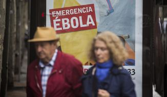 "People walk past an advert calling for financial help to fight Ebola in Africa on Friday, Oct. 10, 2014 in Madrid downtown, Spain. A Spanish hospital official says the nursing assistant Teresa Romero, infected with Ebola, is ""stable,"" hours after authorities described her condition as critical. Romero is the first person known to have caught the disease outside the outbreak zone in West Africa, contracting the virus while helping treat a Spanish missionary who became infected in West Africa, and later died. (AP Photo/Santi Palacios)"
