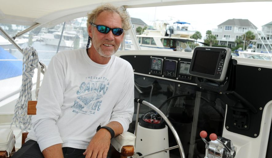 """ADVANCE FOR USE MONDAY, OCT. 13 - In this photo taken on Sept. 16, 2014, David Lawn poses for a photo in his 42-foot catamaran the """"Sea Angel"""" in Carolina Beach, N.C. Lawn will sail to the South Pacific as part of the non-profit Sea Mercy that provides free floating health care clinics. (AP Photo/The Star-News, Mike Spencer)  LOCAL TELEVISION OUT; LOCAL INTERNET OUT"""