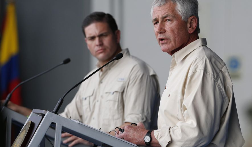 U.S. Defense Secretary Chuck Hagel, right, speaks at a press conference at the Tolemaida military base, in Melgar, Colombia, Friday, Oct. 10, 2014. Hagel is on a six-day, three-country trip to South America. Hagel will also travel to Chile and Peru, where he will attend a conference of defense ministers from the Americas. Pictured left is  Colombia's Defense Minister Juan Carlos Pinzon. (AP Photo/Fernando Vergara)