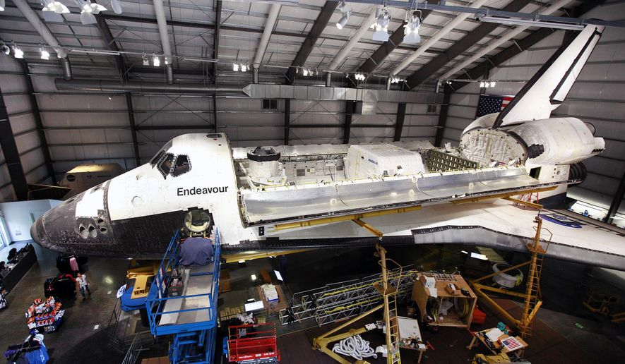 The payload bay doors of the space shuttle Endeavour, housed at the California Science Center, stand open after the installation of a space lab and storage pod on Friday, Oct. 10, 2014 in Los Angeles. The equipment being installed was flown on some missions. A crew on Thursday delicately positioned the 3,000-pound (1,360-kilogram) portable lab and pod inside the orbiter's huge cargo bay. Workers also installed a replica robotic arm, airlock and docking system. (AP Photo/Richard Vogel)