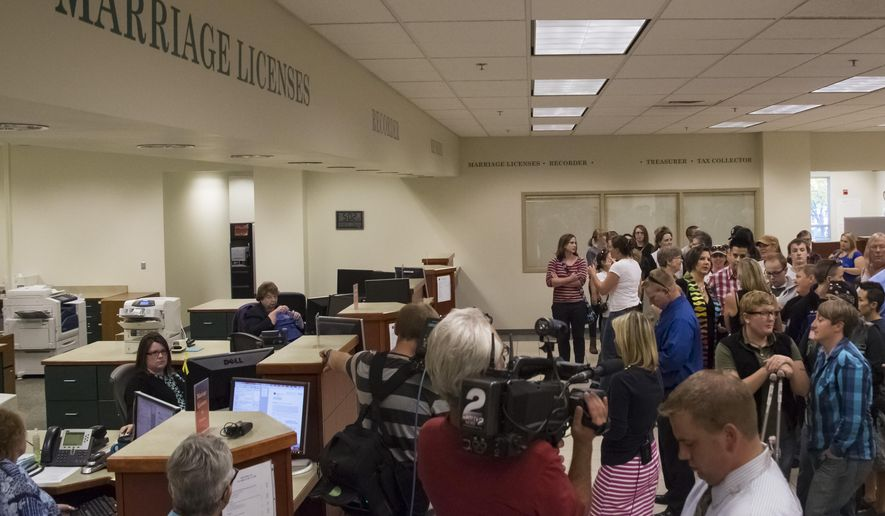 Couples line up for same sex marriage licenses forms at the Ada County Courthouse in Boise, Idaho on Friday, Oct. 10, 2014. Although the U.S. Supreme Court issued an order Friday that appears to have cleared the way for gay marriages in conservative Idaho, without word from the 9th Circuit Court, the Idaho attorney general did not give the order to issue licenses before the office closed for the day. (AP Photo/Otto Kitsinger)