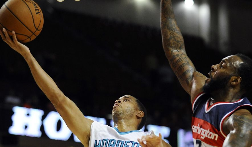 Charlotte Hornets guard Jannero Pargo (5) goes to the basket as Washington Wizards forward Damion James (7) defends during the second half of a preseason NBA basketball game, Friday, Oct. 10, 2014, in Greenville, S.C. (AP Photo/Rainier Ehrhardt)