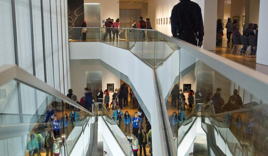 Advance Security guard Damere Lindsay, top, watches ArtPrize patrons inside the Grand Rapids Art Museum Tuesday, Oct. 7, 2014. (AP Photo/The Grand Rapids Press, Cory Morse)