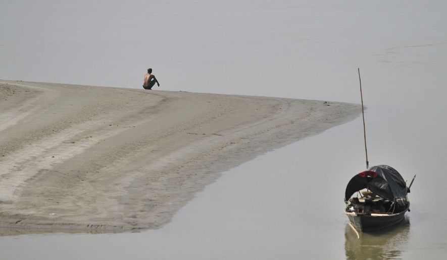 An Indian man urinates on the banks of the River Brahmaputra in Gauhati, India, Friday, Oct. 10, 2014. India is considered to have the world's worst sanitation record despite spending some $3 billion since 1986 on sanitation programs, according to government figures. Building toilets in rural India, where hundreds of millions are still defecating outdoors, will not be enough to improve public health, according to a study published Friday. (AP Photo/Anupam Nath)
