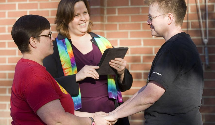 Tabitha Simmons, left, and Katherine Sprague, right, are married by Rev. Elizabeth Stevens, from the Unitarian Universalist Church of the Palouse, outside the Latah County Courthouse in Moscow, Idaho, on Friday, Oct. 10, 2014. Sprague and Simmons were the first couple to be issued a same-sex marriage license in Latah County. (AP Photo/Moscow-Pullman Daily News, Geoff Crimmins)