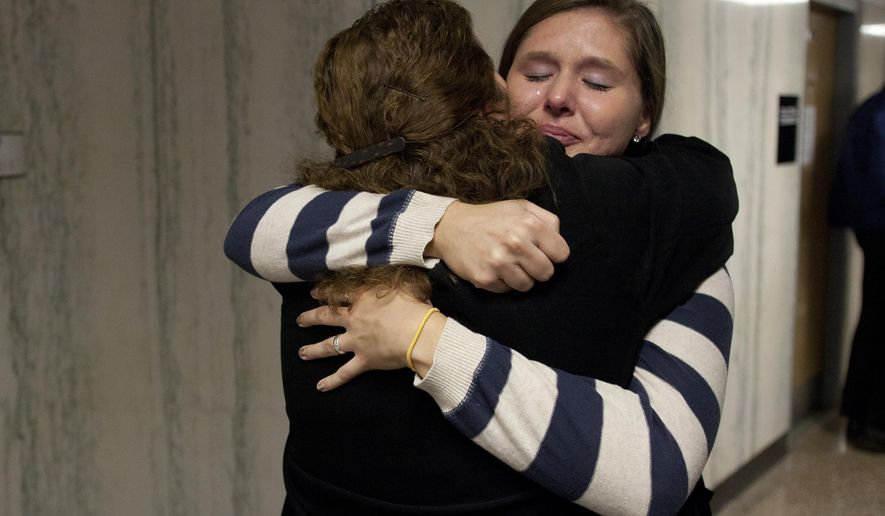 Rebekah DeWolf hugs a detective outside Washtenaw County Trial Court, Friday, Oct. 10, 2014, in Ann Arbor, Mich., after a jury found Dajeon Franklin guilty in the fatal shooting of her brother Paul DeWolf, a 25-year-old University of Michigan medical student. Franklin, 22, convicted of first-degree home invasion, conspiracy to commit home invasion, second-degree home invasion and felony firearm, is scheduled to be sentenced Nov. 19. (AP Photo/The Ann Arbor News, Patrick Record) LOCAL TELEVISION OUT; LOCAL INTERNET OUT
