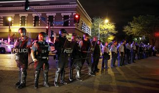 Police wearing riot gear form a line to contain protesters Thursday, Oct. 9, 2014, a day after Vonderrit D. Myers was shot and killed by white, off-duty St. Louis police officer in St. Louis. Police say Myers was shot Wednesday after he opened fire on the off-duty officer, but Myers' parents say he was unarmed. (AP Photo/Jeff Roberson)