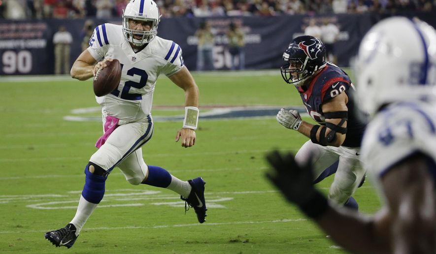 Indianapolis Colts' Andrew Luck (12) tries to escape Houston Texans' J.J. Watt (99) during the second quarter of an NFL football game, Thursday, Oct. 9, 2014, in Houston. (AP Photo/David J. Phillip)