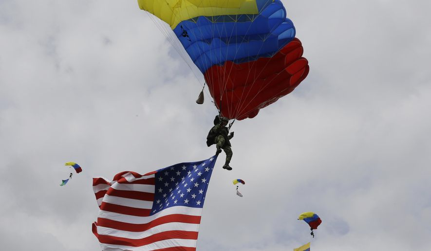 Colombian airborne troops parachute in a show of military exercises at the Tolemaida military base during a visit by U.S. Defense Secretary Chuck Hagel, in Melgar, Colombia, Friday, Oct. 10, 2014. Colombia's was Hagel's first stop on his six-day, three-country trip to South America. Hagel will also travel to Chile and Peru, where he will attend a conference of defense ministers from the Americas. (AP Photo/Fernando Vergara)
