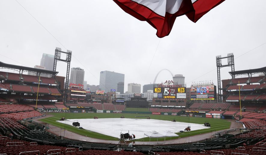 A tarp covers the infield in Busch Stadium, Friday, Oct. 10, 2014, in St. Louis. The St. Louis Cardinals and the San Francisco Giants are scheduled to start the NL Championship Series on Saturday in St. Louis. (AP Photo/Charlie Neibergall)