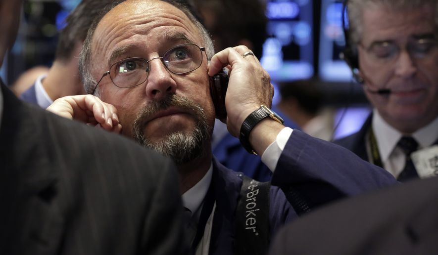 Trader Frederick Reimer uses his mobile phone as he works on the floor of the New York Stock Exchange, Friday, Oct. 10, 2014. Lingering investor jitters about the global economy weighed on U.S. markets, pushing stocks mostly lower in morning trading Friday.  (AP Photo/Richard Drew)