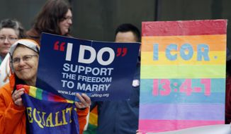 Lin Davis, of Juneau, Alaska, shown wearing an orange rain coat, holds signs supporting gay marriage during a news conference Friday, Oct. 10, 2014, outside the federal courthouse in Anchorage, Alaska. A federal judge on Friday heard arguments from five gay couples seeking to overturn the state's ban on gay marriage. (AP Photo/Mark Thiessen)