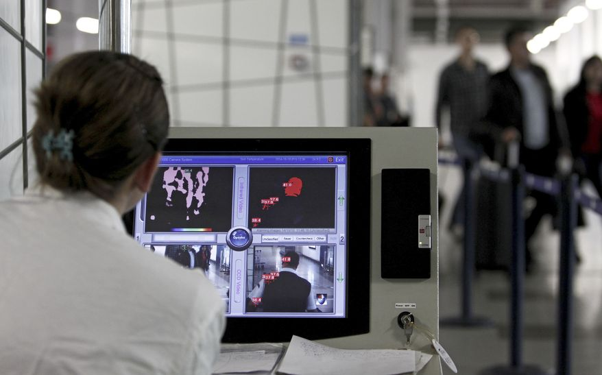 A health worker scans skin temperature of the passengers with a thermal imaging camera upon their arrival at Alexander the Great airport near Macedonia's capital Skopje, Friday, Oct. 10, 2014. Macedonian health officials said Friday that there are small chances that the British traveler who had died Thursday in Skopje was infected by Ebola virus. (AP Photo/Boris Grdanoski)