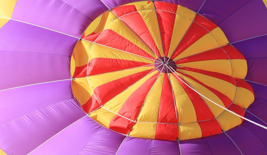 A spectator walks by as a hot air balloons is inflated during the annual Albuquerque International Balloon Fiesta in Albuquerque, N.M., on Saturday, Oct. 11, 2014. The nine-day event, which wraps up Sunday, Oct. 12, attracts hundreds of pilots from around the world and tens of thousands of spectators. (AP Photo/Susan Montoya Bryan)