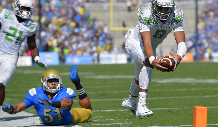 Oregon quarterback Marcus Mariota, right, dives in for a touchdown as UCLA linebacker Aaron Wallace, center, misses the tackle and running back Royce Freeman looks on during the first half of a NCAA college football game, Saturday, Oct. 11, 2014, in Pasadena, Calif. (AP Photo/Mark J. Terrill)