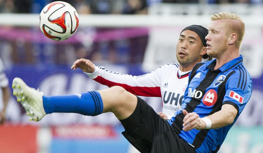 Montreal Impact's Calum Wallace, right, and New England Revolution's Lee Nguyen battle for the ball during first half of an MLS soccer game in Montreal, Saturday, Oct. 11, 2014. (AP Photo/The Canadian Press, Graham Hughes)