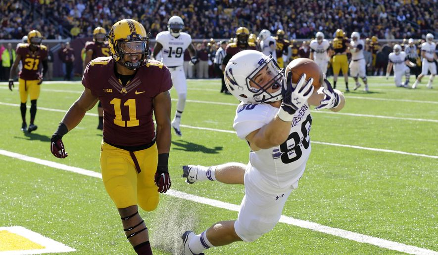 Northwestern wide receiver Austin Carr (80) pulls in a pass in front of Minnesota defensive back Antonio Johnson (11) but lands out-of-bounds for an incomplete pass during the fourth quarter of an NCAA college football game in Minneapolis ON Saturday, Oct. 11, 2014. Minnesota won 24-17. (AP Photo/Ann Heisenfelt)