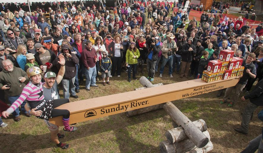 """This photo courtesy of Sunday River Communications, Jesse Wall and Christina Arsenault weigh in during the the North American Wife Carrying Championship on Saturday, Oct. 11, 2014, in Newry, Maine.  Wall carried Christina Arsenault over a 278-yard course that was bedeviled by log hurdles, sand traps and a """"widow maker"""" water hazard at Sunday River ski resort on Saturday to claim the crown in a time of 1 minute, 4.1 seconds. About 50 couples competed.  (AP Photo/Courtesy Sunday River Communications, Nick Lambert)"""