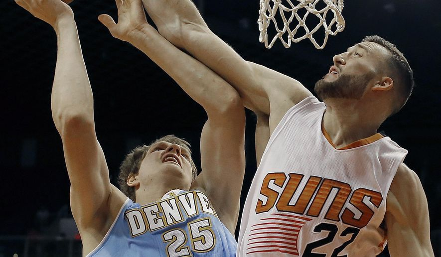 Denver Nuggets center Timofey Mozgov (25) gets foled by Phoenix Suns center Miles Plumlee (22) in the first quarter during an preseason NBA basketball game, Friday, Oct. 10, 2014, in Phoenix. (AP Photo/Rick Scuteri)