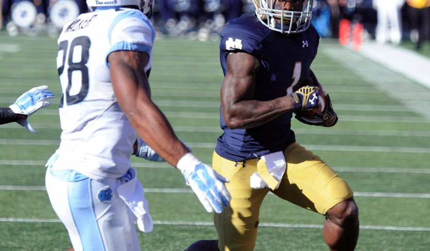 Notre Dame running back Greg Bryant, right, heads upfield as North Carolina cornerback Brian Walker closes in the first half of an NCAA college football game, Saturday, Oct. 11, 2014, in South Bend, Ind. (AP Photo/Joe Raymond)