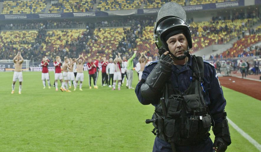 Hungary's players celebrate as a riot police officer stands by at the end of the Group F, Euro 2016 qualifying match between Romania and Hungary, at the National Arena stadium, in Bucharest, Romania, Saturday, Oct. 11, 2014. (AP Photo/Vadim Ghirda)