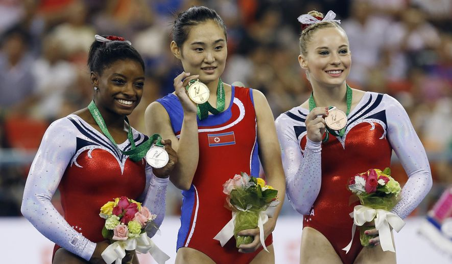 Gold medalist Hong Un Jong of North Korea, center, second place Simone Biles of the U.S., left, and third place Mykayla Skinner of U.S. pose for photos on podium during the award ceremony of the women's vault apparatus final of the Artistic Gymnastics World Championship at the Guangxi Gymnasium in Nanning, capital of southwest China's Guangxi Zhuang Autonomous Region Saturday, Oct. 11, 2014. (AP Photo/Andy Wong)