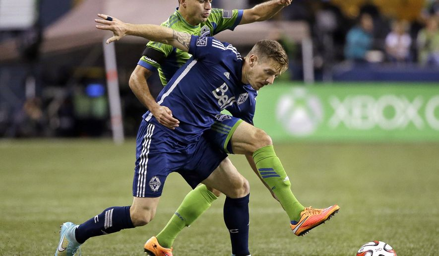 Vancouver Whitecaps' Jordan Harvey, right, and Seattle Sounders' Marco Pappa collide as they race toward the ball in the first half of an MLS soccer game Friday, Oct. 10, 2014, in Seattle. (AP Photo/Elaine Thompson)